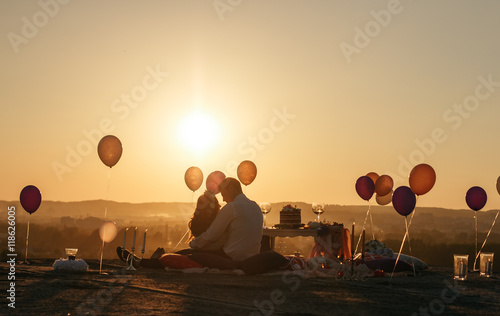 Colorful balloons sore around man and woman lying on the roof