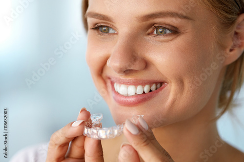 Fotografia  Smiling Woman With White Teeth Holding Teeth Whitening Tray