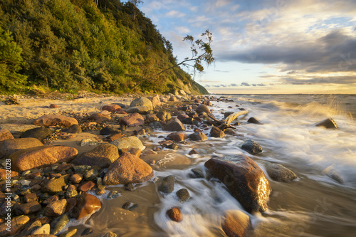 Sea landscape at sunset, sandy beach and cliff,waves breaking on the shore