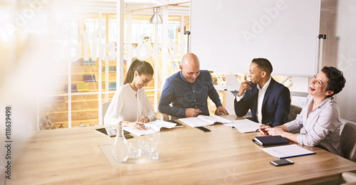 obraz PCV business professionals laughing during a meeting between the electoral board because of a joke that was told by one of the individuals during the meeting to lighten the mood.