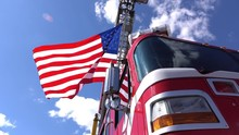 American Flag Waves In The Wind From The Ladder Of A Big Red Firetruck.