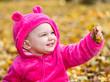 Leinwandbild Motiv Cute baby girl sitting in autumn leaves