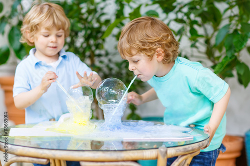 Fotografie, Obraz  two twin boys making experiment with colorful bubbles
