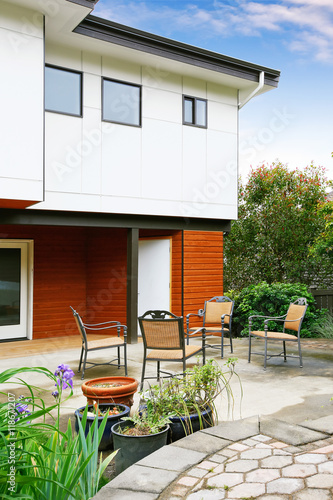 Fotobehang Tuin Cozy concrete floor patio area with table set near the modern city house.