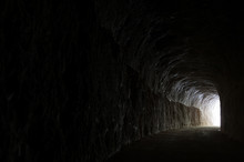 Dark Road In A Natural Rocky Tunnel And The Light Of The Exit