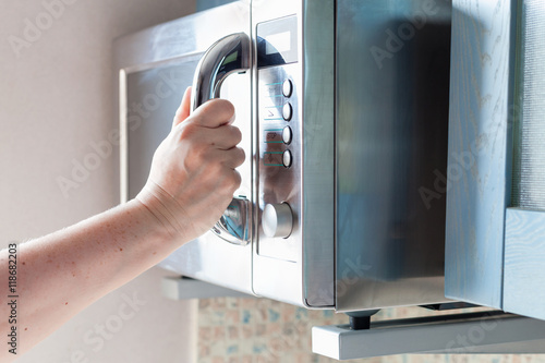 hand closes microwave oven for cooking food