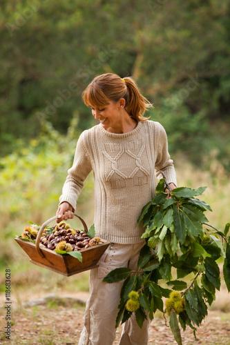 Foto op Plexiglas Aap femme souriant avec un panier et des branches de châtaignier
