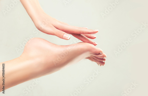 Foto op Aluminium Pedicure Perfect clean female feet . Beautiful women's hand touches her well-groomed feet. Spa ,scrub and foot care .