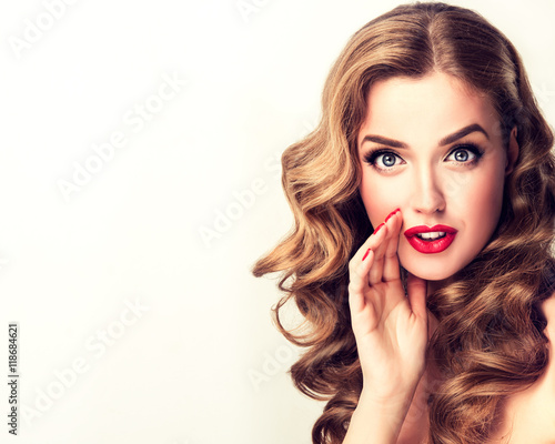 Fototapeta Beautiful girl with bright makeup and curly hair   telling   a secret