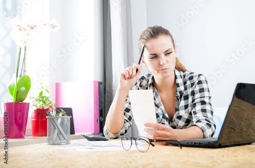Obraz na plátne  Woman calculating and paying bills in home office