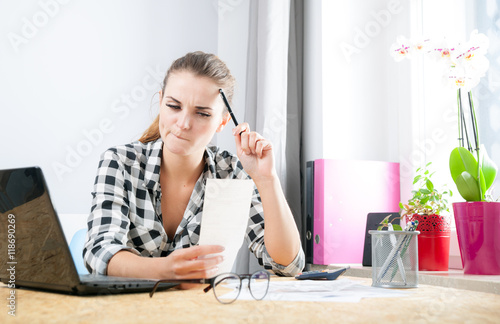 Fotografia, Obraz  Woman calculating and paying bills in home office