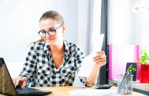 Fotografia, Obraz  Smiling woman calculating and paying bills in home office