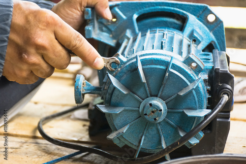 Fotografia, Obraz  Electric motor and man working equipment repair on wooden floor background