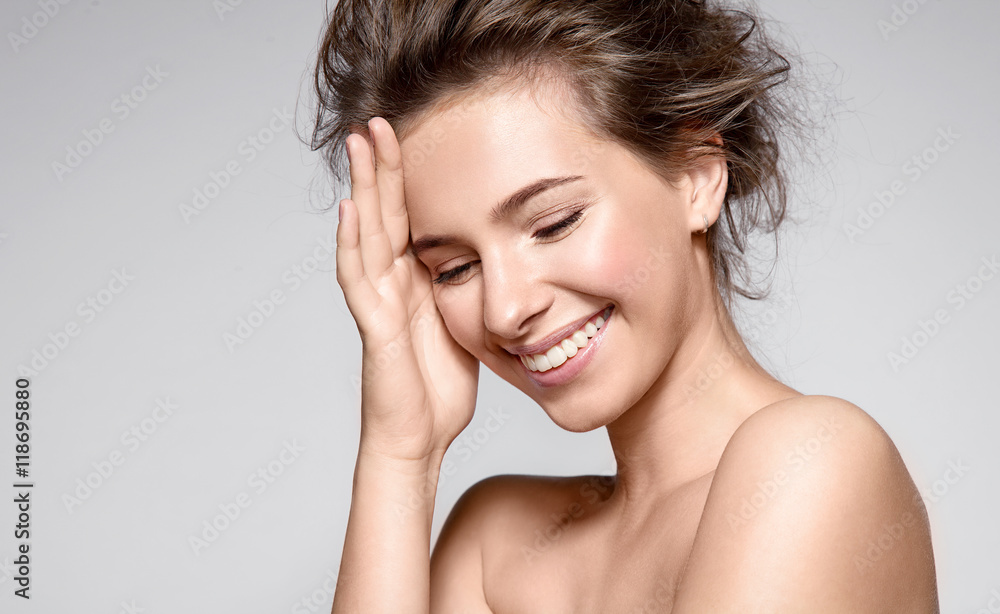 Beautiful smiling woman with natural make-up, clean skin and white teeth on grey background
