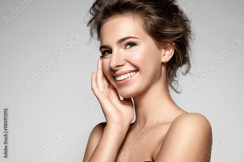 Fotografía  Beautiful smiling girl with clean skin, natural make-up, and white teeth on grey