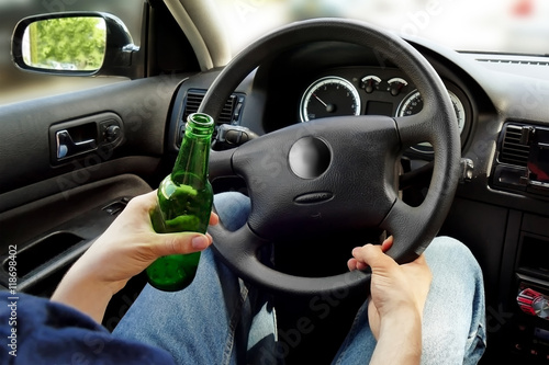 Fotografie, Obraz  Unrecognizable man drinking and driving. Dangerous driving conce