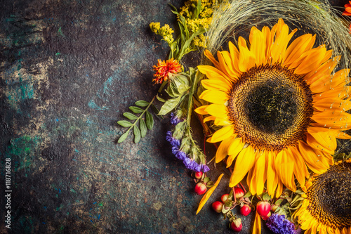 In de dag Zonnebloem Sunflowers with berries and flowers. Floral autumn decoration on dark rustic vintage background, top view, border