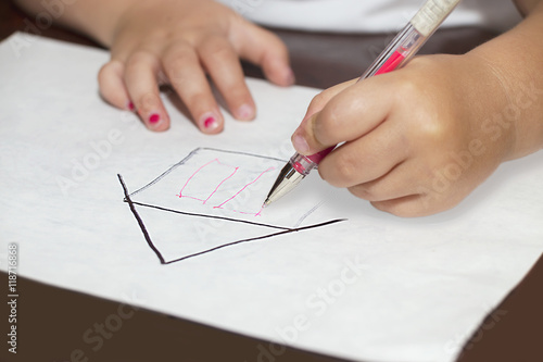 Little girl's hands with ballpen drawing a house