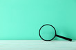 canvas print picture - Magnifying glass on a green wooden table