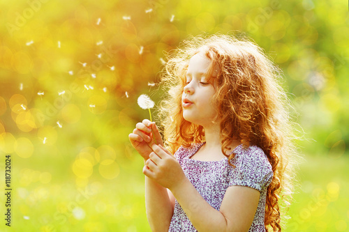 Little curly girl blowing dandelion. Canvas Print