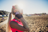 Fototapeta Sport - sport outdoor photo of beautiful young blonde woman in pink colorful sport suit listening to music on headphones by the beach