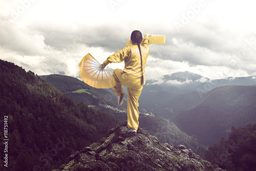 Fotografia  woman practicing tai chi on the mountain