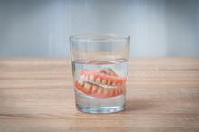 False Teeth Swim In Transparent Water Glass