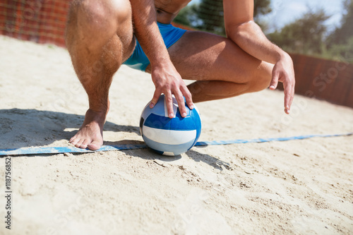 Beach volleyball - Young handsome man holding a ball for beach volleball game Poster