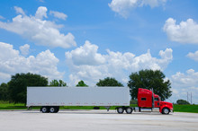 Clean Shiny Red 16-wheel Semi Tractor Truck With A Clean White Cargo Container Trailer Against A Simple Colorful Background Of Trees And Blue Sky