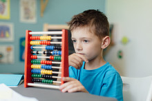 Back To School. Portrait Of A Thinking School Boy Learning Maths With An Abacus.
