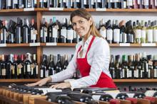 Saleswoman Arranging Wine Bottles In Rack