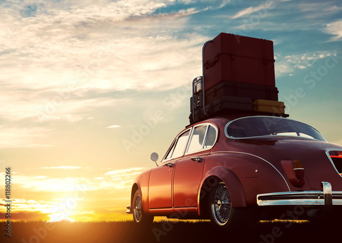 Fotografia  Retro red car with luggage on roof rack at sunset