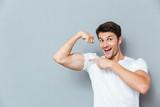Smiling man pointing on his biceps