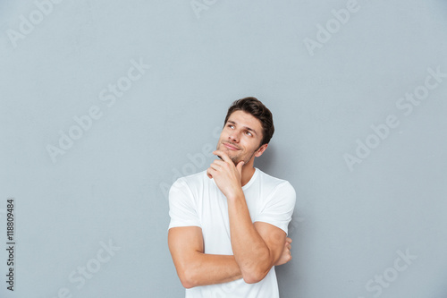Fotografía  Pensive attractive young man smiling and thinking