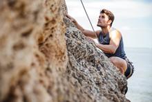 Young Man Climbing Natural Roc...