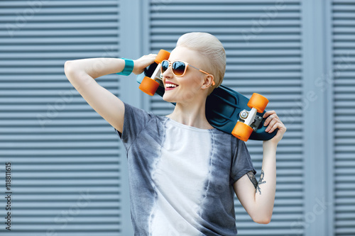 Fotografía  Young woman with short blonde hair smiling on the fashion background and holding little penny skateboard behind her head and looking awawy