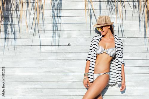 sexy woman in bathing suit standing in sunlight Wallpaper Mural