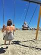 mamma e bimba sull'altalena in spiaggia