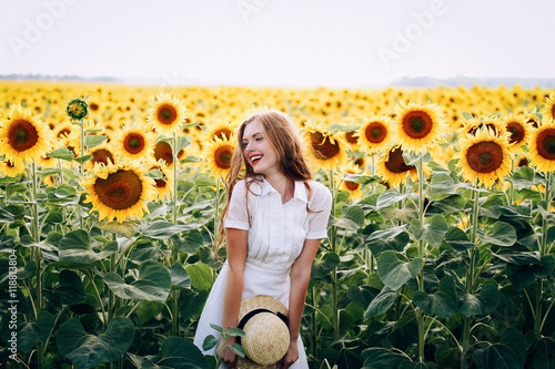 beautiful sweet sexy girl in a white dress walking on a field of sunflowers , sm Fototapet