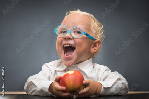 Fotografie, Tablou  Cheerful baby on a gray background with a white shirt eating an