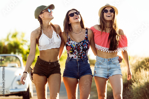 Fotografia  Three beautiful young women enjoying summer on road trip.