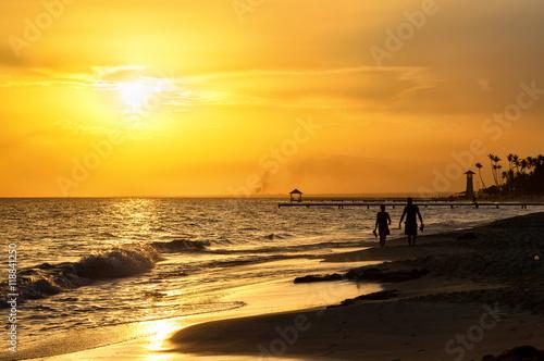 Foto op Plexiglas Caraïben Silhouette of children running along the coastline. Caribbean sea beach sunset. Tropical beach in Caribbean sea, Dominican Republic. Couple are waiting sunset in Caribbean beach. .