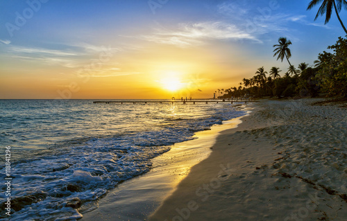Foto op Plexiglas Caraïben Silhouette of children running along the coastline. Caribbean sea beach sunset. Tropical beach in Caribbean sea, Dominican Republic. Couple are waiting sunset in Caribbean beach. .