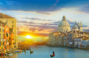 Beautiful panoramic view over the famous Grand canal in Venice, surrounded by old and romantic architecture illuminated by sun at sunrise, in Italy