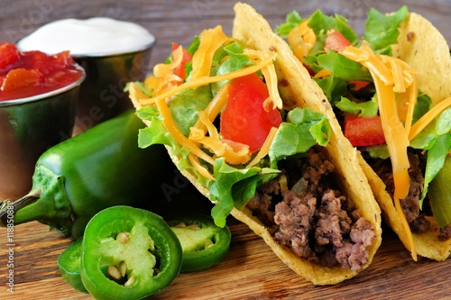 Fényképezés  Hard shelled tacos with ground beef, lettuce, tomatoes and cheese close up, on r