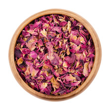 Dried Rose Petals In A Wooden Bowl On White Background. Used For Perfums, Cosmetics, Teas And Baths. Purple Colored Organic Herb. Isolated Macro Photo Close Up From Above.