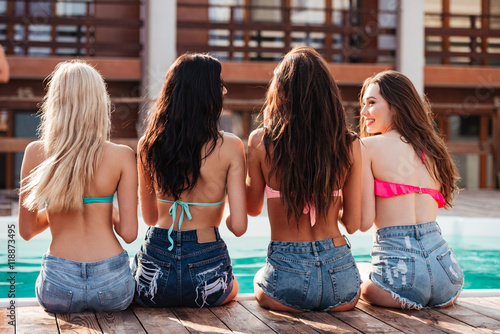Fotografija  Back view of cheerful young women talking near swimming pool