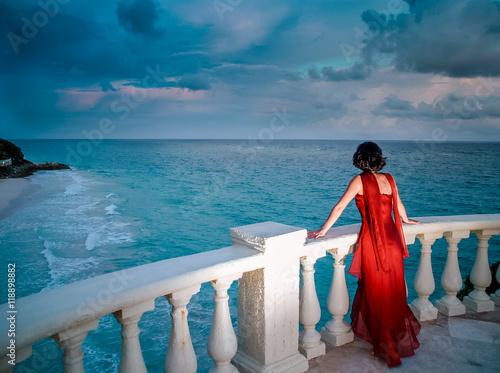Fotografia, Obraz  Elegant Lady In Red Dress Standing By Ocean At Sunset