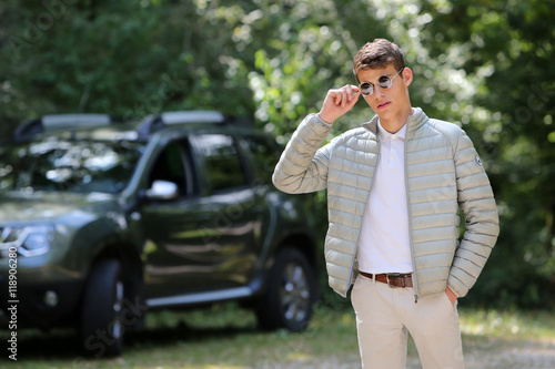 Foto  Young man with sunglasses and 4x4