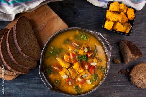 Fototapeta Zupa dyniowa z pomidorami i ziołami w stylu rustykalnym.